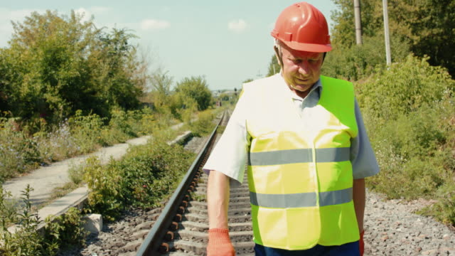 A senior mechanical engineer in uniform walks along the track in summer video