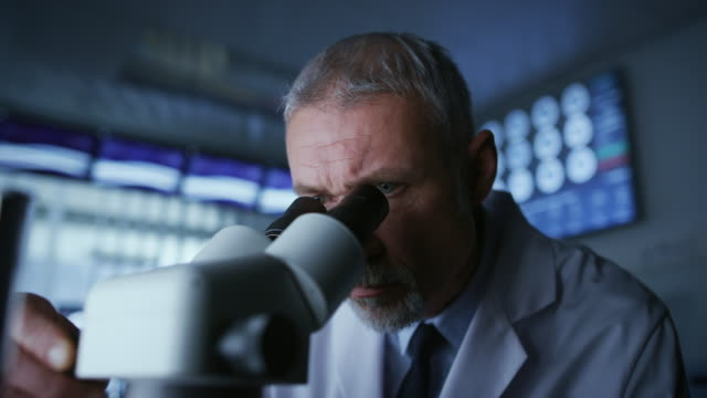 Senior Medical Research Scientist Looking under the Microscope in the Laboratory. Neurologist Solving Puzzles of the Mind and Brain. In the Laboratory with Multiple Screens Showing MRI / CT Brain Scan Images.