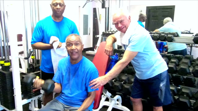 Senior men at gym, friends working out, talking video