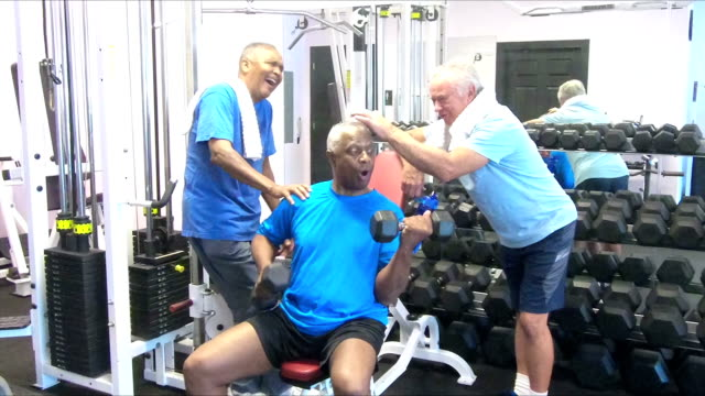 Senior men at gym talking and working out video