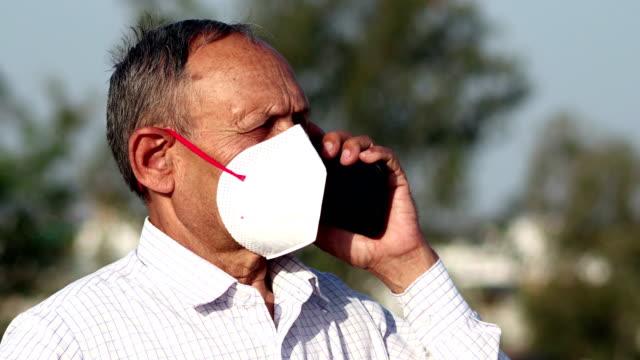 Homens idosos cobrindo seu rosto com máscara de poluição para proteção contra COVID-19 e falando no celular - vídeo
