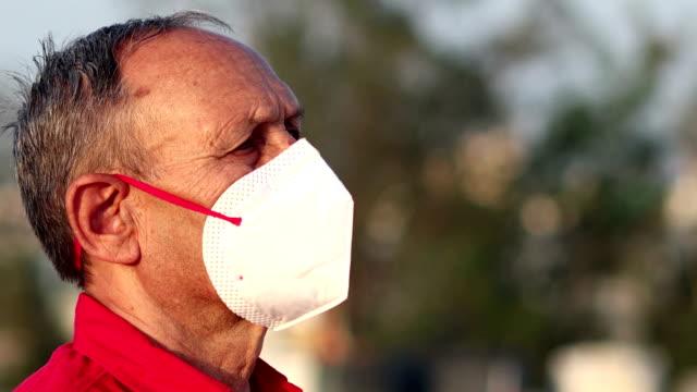 Homens idosos cobrindo seu rosto com máscara de poluição para proteção contra vírus - vídeo