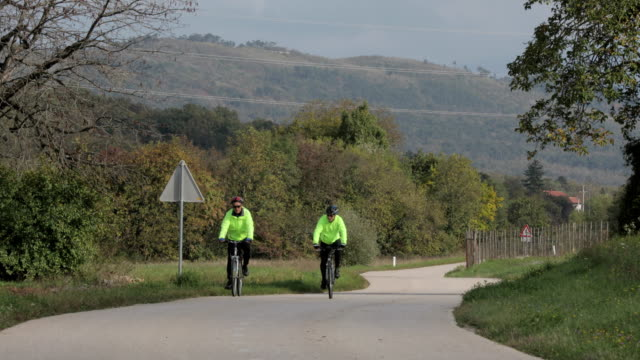Senior Men Friends Cycling Side By Side on Country Road