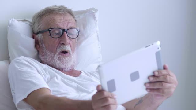 Senior men playing tablet