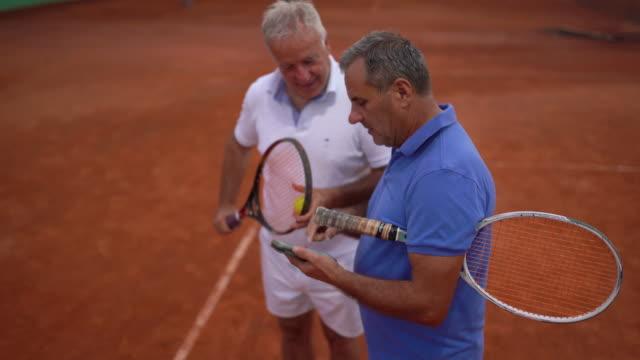 Senior men tennis players using smart phone together on tennis court video