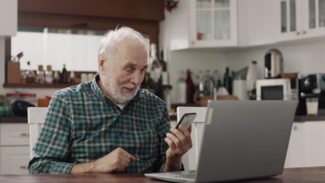 vídeos de stock e filmes b-roll de senior men texting - old men window