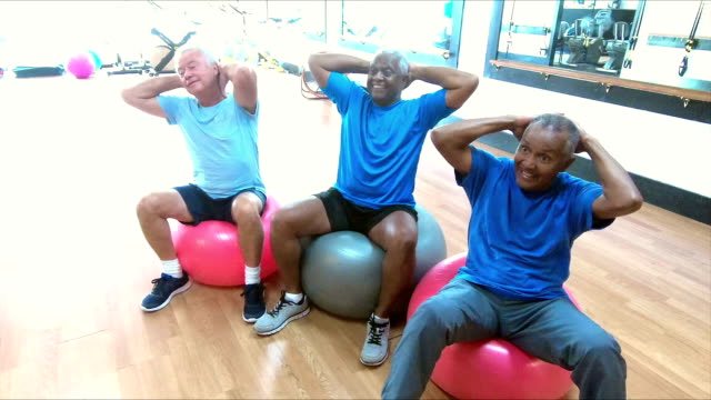 Senior men working out at gym on fitness balls video