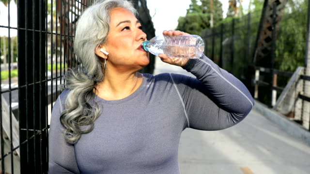 senior mexican woman drinking water - capelli grigi video stock e b–roll