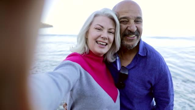 vídeos de stock e filmes b-roll de senior mixed couple taking a selfie at the beach - atividade recreativa