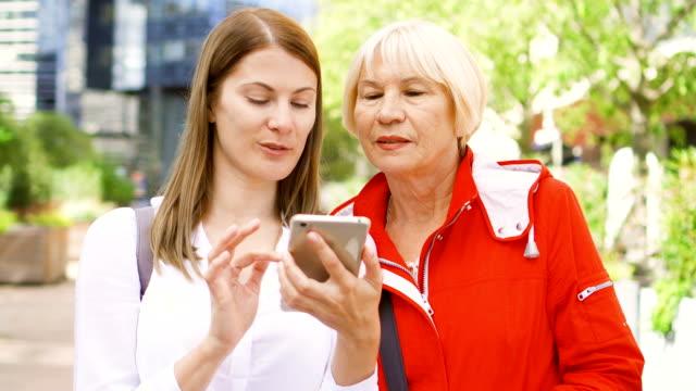 先輩の母とスマート フォンを使用して路上に立っている彼女の若い娘。幸せな家庭を一緒に ビデオ