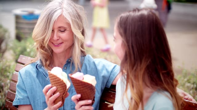 Senior mother and young daughter eating ice cream at park