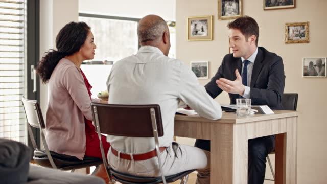vídeos de stock, filmes e b-roll de sênior de multi étnica casal consultoria pessoal banqueiro em casa - dia do cliente