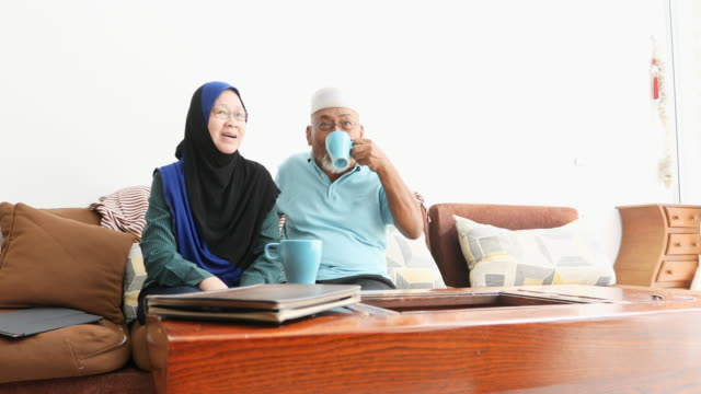 senior muslim asian couple drinking tea and watching television - etnia malese video stock e b–roll