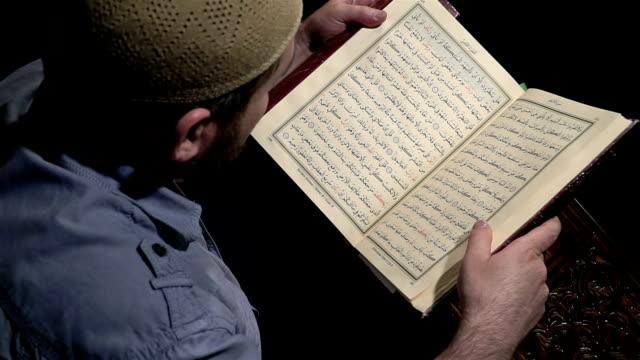stockvideo's en b-roll-footage met senior islamitische imam lezen in donker - koran