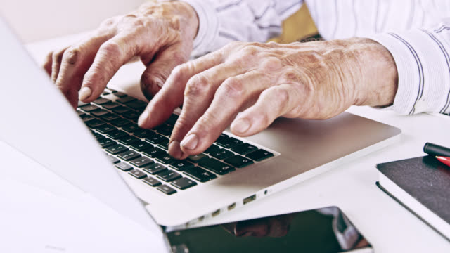 DS Senior office worker typing on a laptop in the office video
