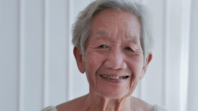 自宅でカメラを見ている先輩の古い白髪の女性。素敵な素敵な高齢女性は素晴らしい気分で笑顔。自宅や退職後の家で歯の笑顔を持つ幸せな長老の成熟した祖母 - 介護点の映像素材/bロール