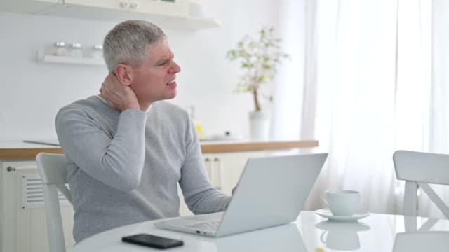 vídeos de stock, filmes e b-roll de idoso velho com laptop tendo dor no pescoço em casa - ortopedia
