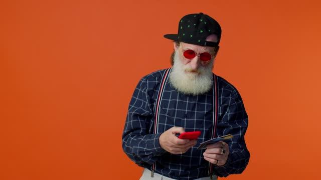 クレジットカードとスマートフォンを使用してシニア古いスタイリッシュなひげを生やした男は、オンラインショッピングを購入します - あごヒゲ点の映像素材/bロール