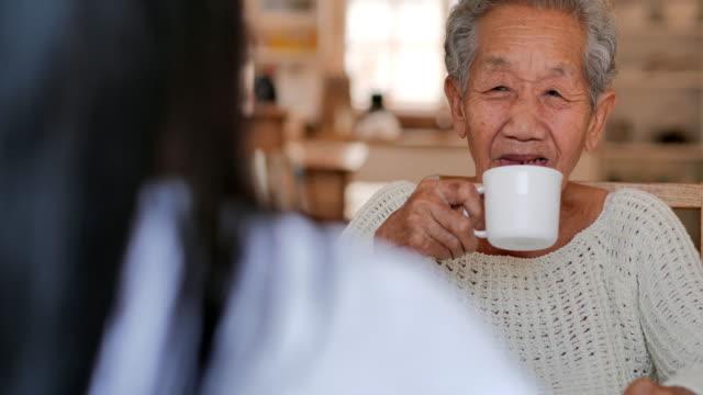 Senior old woman talking to young black female nurse help patient at medical consultation at home.Elderly grandmother listen caregiver giving support,Older people healthcare,Medical,Caretaking,Care,Retirement,Volunteer,Nursing home.At Home Caregiver video
