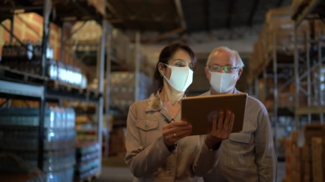 senior partners walking and using digital tablet at warehouse - with face mask - prodotti supermercato video stock e b–roll