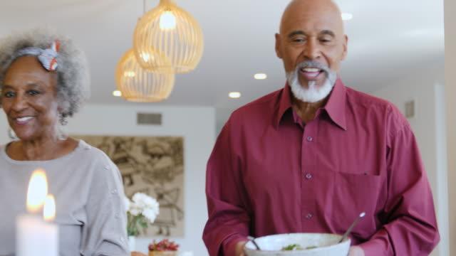 vídeos de stock, filmes e b-roll de anfitriões seniores do partido que servem comida vegana aos hóspedes - vegetarian meal