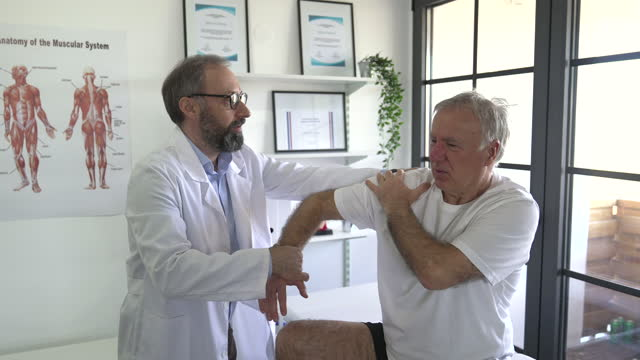 Senior patient and physiotherapist discussing about his recovery at doctor's office Senior patient and physiotherapist discussing about his recovery at doctor's office general practitioner stock videos & royalty-free footage