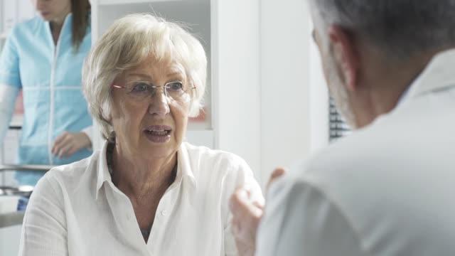vídeos de stock, filmes e b-roll de paciente sênior que encontra o doutor no escritório - geriatria