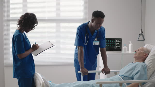 Senior patient on bed talking to 2 African American doctor in hospital room, Health care and insurance concept. Doctor comforting elderly patient in hospital bed or counsel diagnosis health.