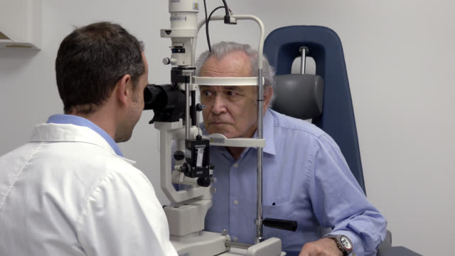 Senior patient with his ophthalmologist who is doing an eye exam Senior patient with his ophthalmologist who is doing an eye exam ophthalmologist stock videos & royalty-free footage