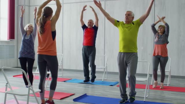 Senior People and Fitness Trainer Doing Aerobics