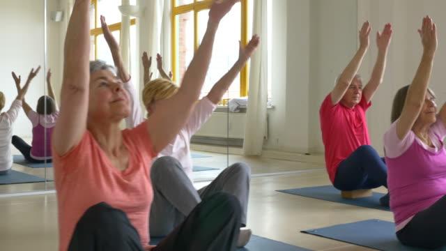 Senior people doing yoga in health club video