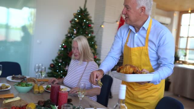 anziani che si godono il doppio appuntamento durante il pranzo a casa - pranzo di natale video stock e b–roll