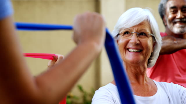 Senior people listening to trainer while exercising with resistance band 4k video
