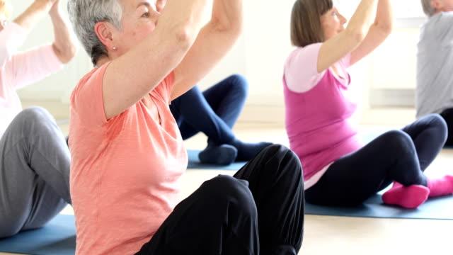 Senior people meditating in yoga class video