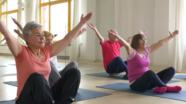 Senior people practicing yoga in class video