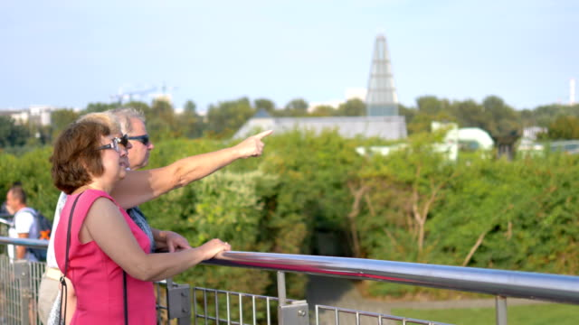 senior people standing at handrail, observing the view and one of them pointing with a finger in 4k slow motion 60fps - balaustrata video stock e b–roll