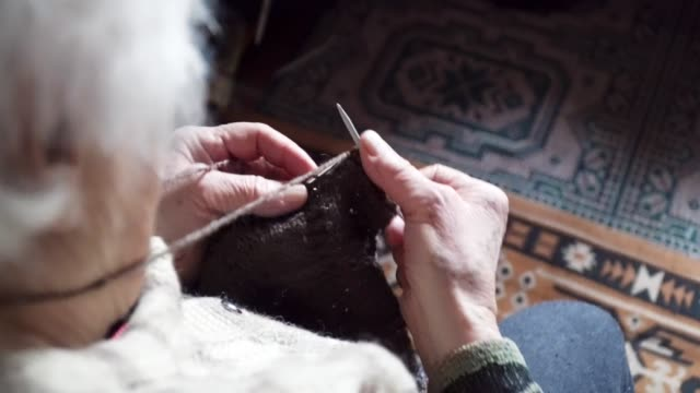 POV. A senior person knitting fine and esthetically, close up of a grandma's hands full of wrinkles working on a new winter sweater, active retirees.
