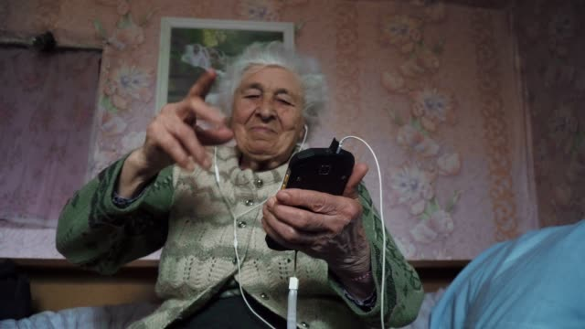 vídeos de stock e filmes b-roll de a senior person listening to music with a set of headphones and a phone, entertainment, medium shot portrait of a grandmother, wrinkles, enjoying the music, dancing with the rhythm, fun, rose background. - música