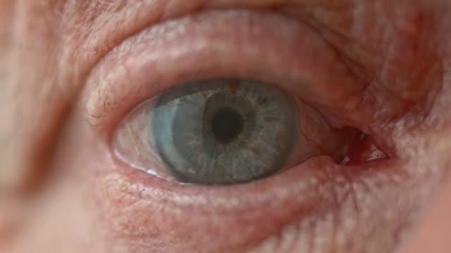 ecu senior persona blu occhio apertura - battere le palpebre video stock e b–roll