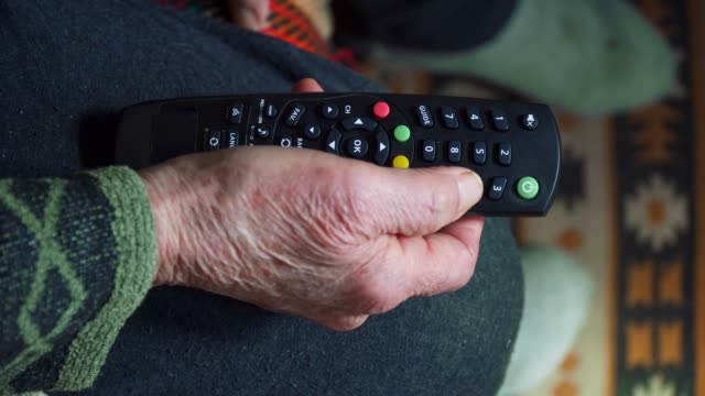 A Senior Person Watching TV, Entertainment, Close up of a grandma's hands full of Wrinkles Using a Remote Controller.