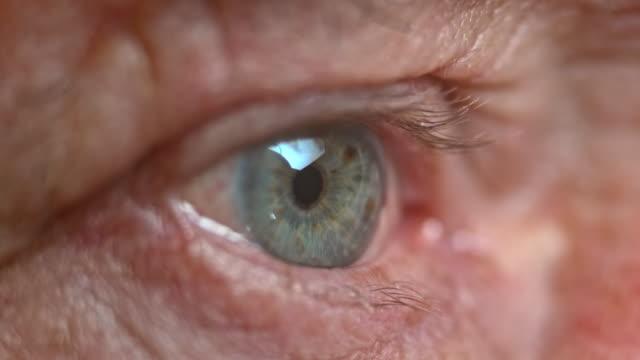 ECU Senior person's blue eye closing video