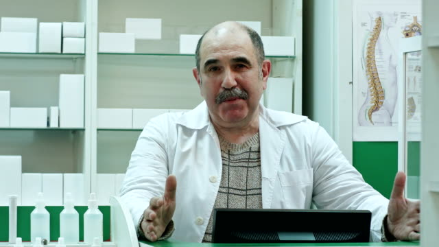 Senior pharmacist talk to a camera presenting medicine advice medical treatment in pharmacy shop video