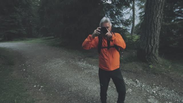 イタリアのドロミテの森でハイキングをするシニアフォトグラファーが写真を撮る - disruptagingcollection点の映像素材/bロール