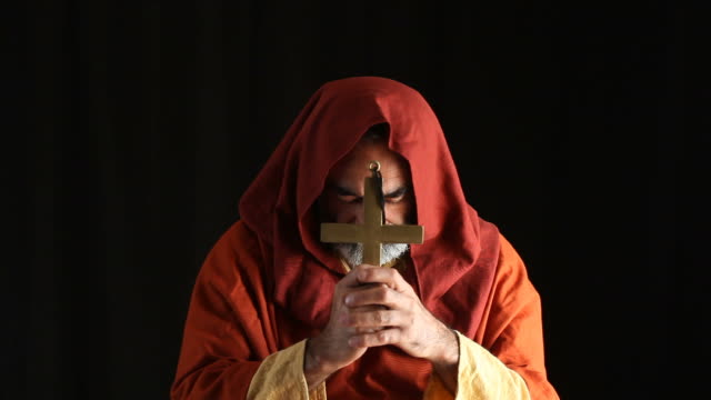 Senior priest praying in dark, cross in hand video