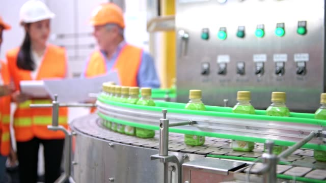 Senior quality inspector teaching junior team member in factory. Chinese old male with his young team discussing quality issue with bottle production line in background. Shot in natural light. quality control stock videos & royalty-free footage