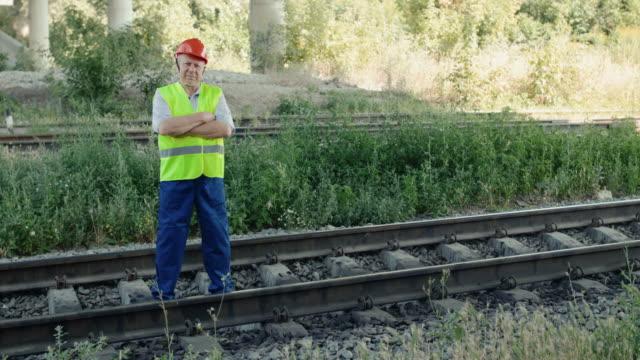 Senior railroader in uniform looking at camera and crossing hands at track video