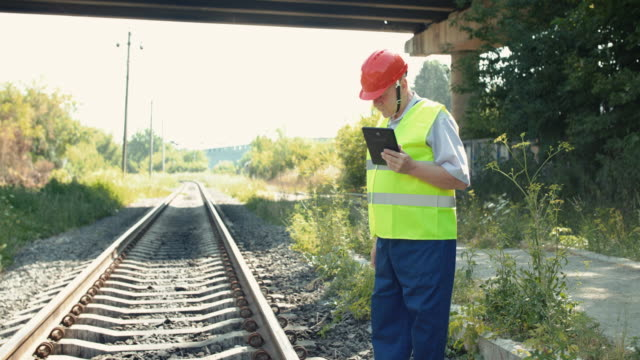 Senior railroader in uniform using tablet when checking serviceability of rails video