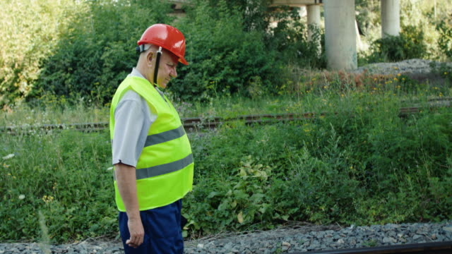 Senior railroader in uniform walking on the railway to check a serviceability video