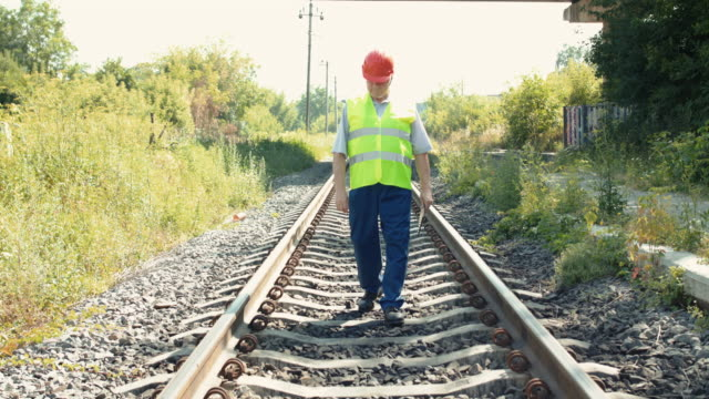 Senior railroader in uniform walking with tablet at the railway video
