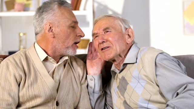 vídeos de stock, filmes e b-roll de homem aposentado sênior com problema da audição que escuta o amigo, uma comunicação - surdo